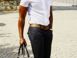 a monochromatic outfit with black pants, a white short-sleeved shirt and a black bag
