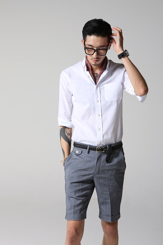 a creative work look with long grey shorts, a white shirt with short sleeves, a neck tie and a statement watch