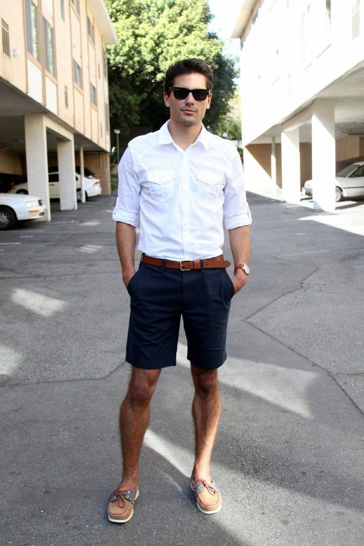 a light summer work look with long navy shorts, a white shirt with rolled up sleeves, brown shoes