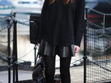 a black leather mini, a black oversized sweatshirt, a statement necklace, black booties and a black bag catch an eye