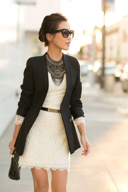 a creamy lace mini dress with your waist highlighted with a belt, a black blazer and black statement necklace plus a black clutch