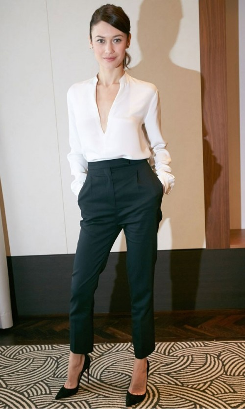a classic monochromatic look with high waisted pants, high heels, a white blouse with a plunging neckline