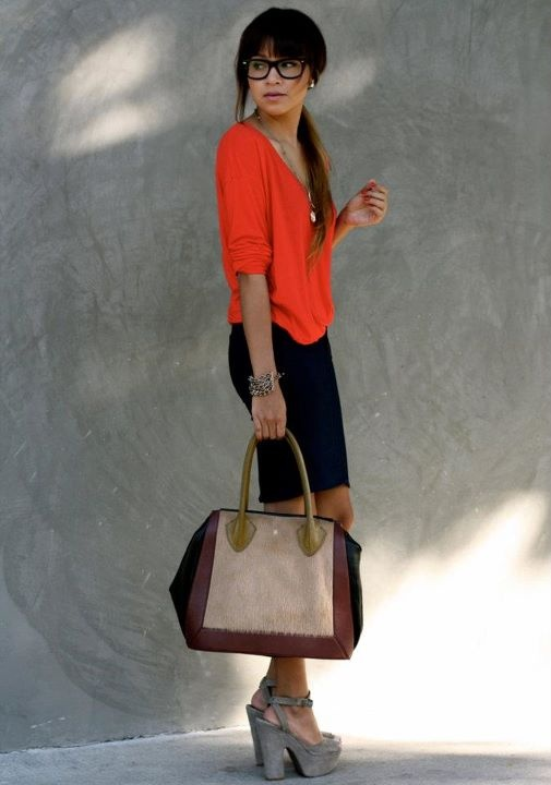a navy pencil mini, an orange top, grey shoes and a color print bag is a playful and bright outfit