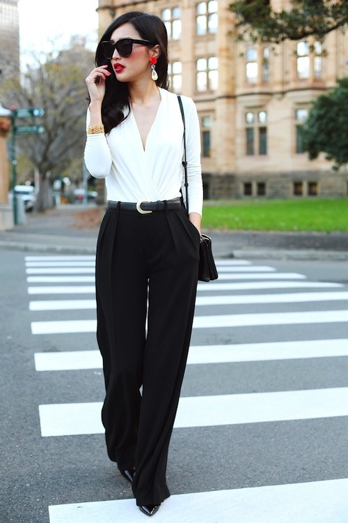 a white blouse with a deep cut is compensated with black widelegs pants, a black bag and black heels